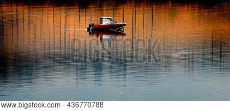 Fishing boat on river with reflection of Fall or Autumn Trees