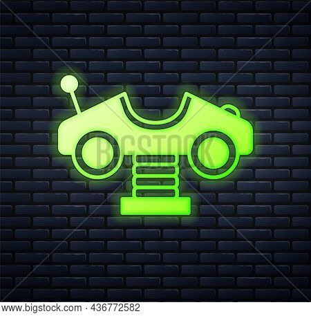 Glowing Neon Swing Car On The Playground Icon Isolated On Brick Wall Background. Childrens Carousel
