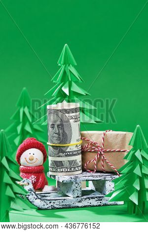 Christmas Scene. Money Christmas Gift On Wooden Sled. Green Origami Fir Tree On A Green Background.