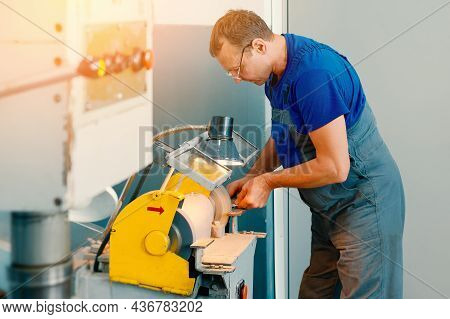 An Adult Turner In Glasses And Working Overalls Works At The Machine. Authentic Scene. Real Workflow