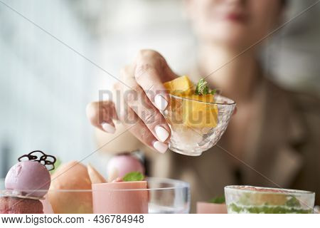 Close-up Shot Of Hands Of An Asian Woman Picking Up A Dessert From Dining Table In Restaurant