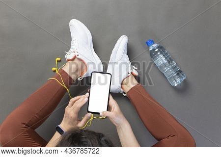 Young Woman Browsing Workout Plan Using Smartphone. Getting Ready For Exercise