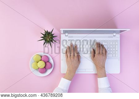 Top View Businesswoman Hands On Trendy Pink Desk In The Office With Laptop.