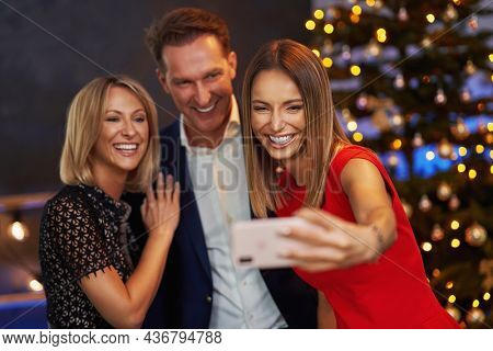 Business friends celebrating christmas party taking selfie. High quality photo