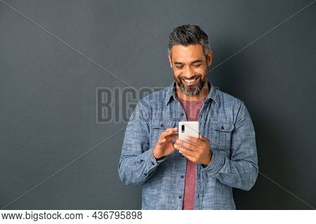 Mid adult multiethnic man texting phone message on smart phone isolated on grey background. Smiling middle eastern man using smartphone on gray wall. Happy mixed race guy using app on mobile phone.