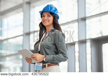 Mid adult woman architect wearing hardhat at construction site while working on digital tablet. Supervisor wearing safety helmet while working in a building site. Successful and proud inspector.