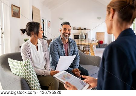 Happy mature couple discussing investments with financial broker during meeting at home. Middle eastern man and woman discussing about financial planning with consultant at home. Financial consultant