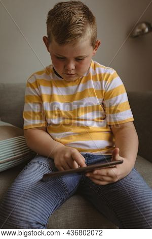 Caucasian boy using digital tablet sitting on the couch at home. childhood, technology and home concept