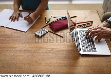 Mid section of father using laptop while son doing his homework at home. home schooling and working from home during coronavirus covid-19 pandemic concept