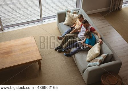 Overhead view of caucasian father and two sons using laptop and digital tablet at home. childhood, technology and home concept