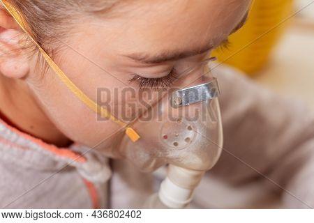 A Little Girl Breathes Through A Compressor Inhaler Mask, Inhaling The Vapor With A Medicinal Soluti