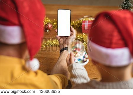 Rear view of father and son having a video call on smartphone with copy space during christmas. social distancing during covid 19 pandemic at christmas time
