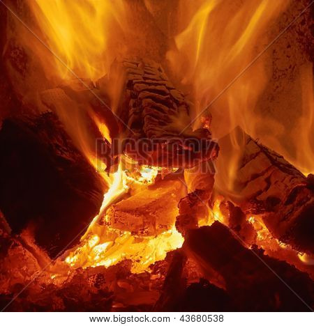 Firewood is burning in the stove. Flame is yellow and white poster