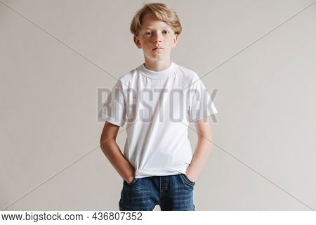 Portrait of a calm casual preteen boy in t-shirt standing over isolated gray wall background holding hands in pockets