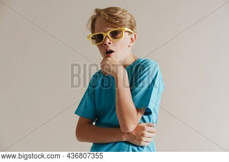 Portrait of a shocked casual preteen boy in t-shirt standing over isolated gray wall background wearing sunglasses