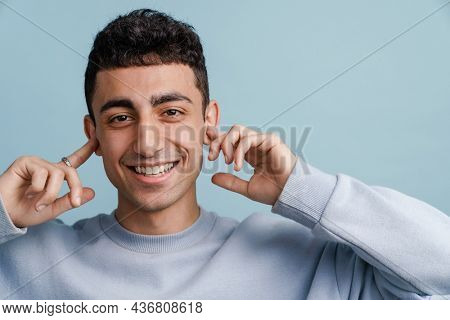 Young middle eastern man smiling and plugging his ears isolated over blue background