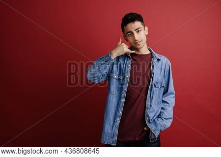 Young middle eastern man smiling while showing handset gesture isolated over red background