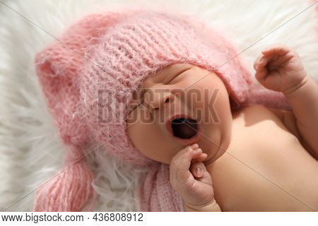 Cute Newborn Baby In Hat Yawning On Fuzzy Blanket, Closeup