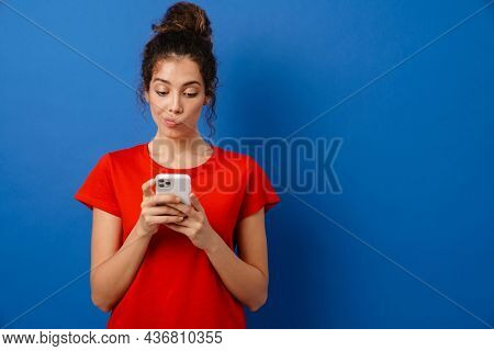 Young brunette woman grimacing while using mobile phone isolated over blue background
