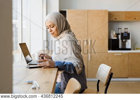 Middle eastern woman in hijab working with laptop and smartphone at office kitchen