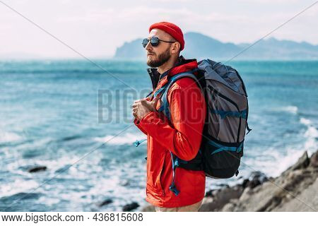 A Bearded Traveler With A Backpack On The Background Of The Sea. Portrait Of A Traveler In Red Cloth