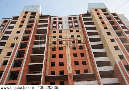 City house under construction. Unfinished multi-storey building. Uncovered facade of the building. Concrete construction is the basis for multi-family housing. Construction site in the city.