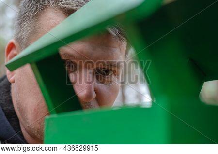 Portrait Of An Adult Male Watching Birds Inside A Bird Feeder. Green Wooden Feeder For Wild Birds In