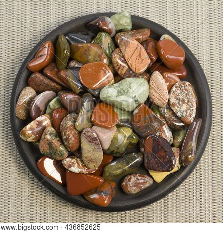 Red And Multicolored Jasper Polished Tumblestones On Black Plate And Grey Background Top View