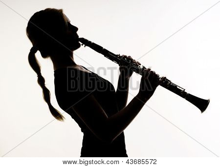 Female Musician In Silhouette Practices Woodwind Technique On Clarinet