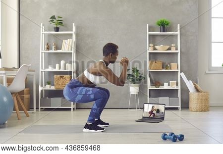Black Woman Doing Squats During Sports Workout At Home With Her Online Fitness Trainer
