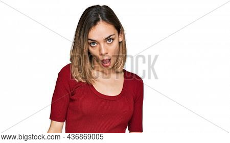 Young blonde girl wearing casual clothes in shock face, looking skeptical and sarcastic, surprised with open mouth