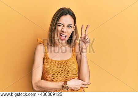 Young caucasian blonde woman wearing casual yellow t shirt smiling with happy face winking at the camera doing victory sign with fingers. number two.