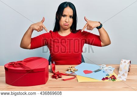 Beautiful hispanic woman with nose piercing doing handcraft creative decoration pointing down looking sad and upset, indicating direction with fingers, unhappy and depressed.