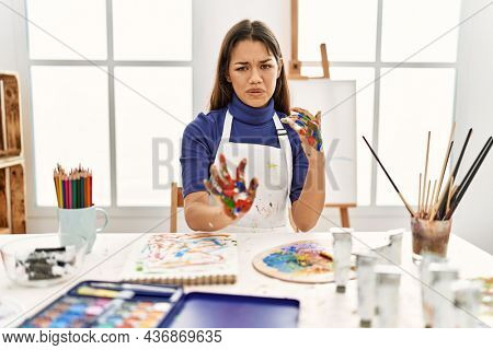 Young brunette woman at art studio with painted hands disgusted expression, displeased and fearful doing disgust face because aversion reaction. with hands raised