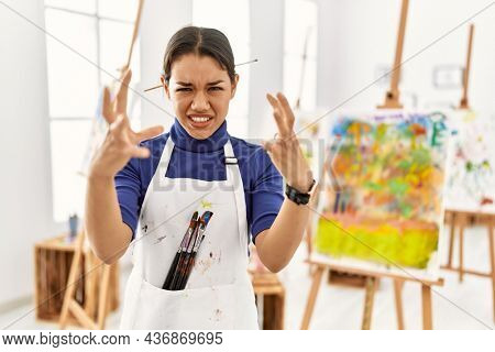 Young brunette woman at art studio shouting frustrated with rage, hands trying to strangle, yelling mad