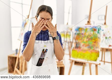 Young brunette woman at art studio rubbing eyes for fatigue and headache, sleepy and tired expression. vision problem
