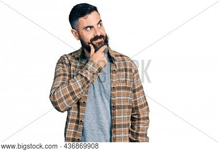 Hispanic man with beard wearing casual shirt with hand on chin thinking about question, pensive expression. smiling with thoughtful face. doubt concept.