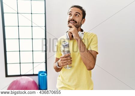 Young hispanic man wearing sportswear and drinking water at the gym with hand on chin thinking about question, pensive expression. smiling and thoughtful face. doubt concept.