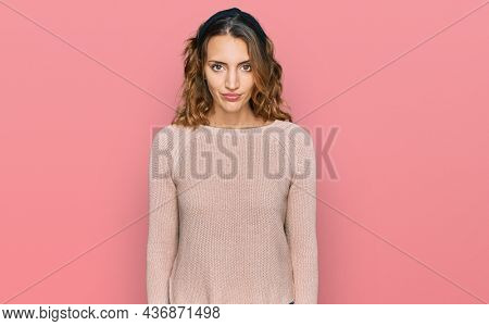 Beautiful young caucasian woman wearing casual sweater looking sleepy and tired, exhausted for fatigue and hangover, lazy eyes in the morning.