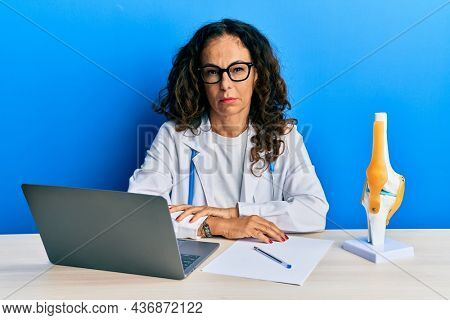 Beautiful middle age woman doctor at orthopedic clinic skeptic and nervous, frowning upset because of problem. negative person.