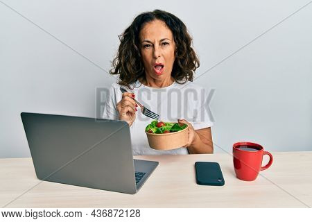 Beautiful middle age woman working at the office eating healthy salad in shock face, looking skeptical and sarcastic, surprised with open mouth
