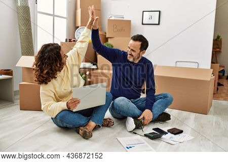 Middle age hispanic couple smiling happy with hands raised up high five. Sitting on the floor at new home.