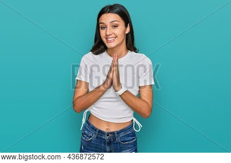 Young hispanic girl wearing casual white t shirt praying with hands together asking for forgiveness smiling confident.