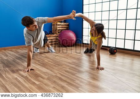 Man and woman couple training abs exercise high five at sport center