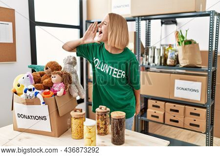 Young caucasian woman wearing volunteer t shirt at donations stand shouting and screaming loud to side with hand on mouth. communication concept.
