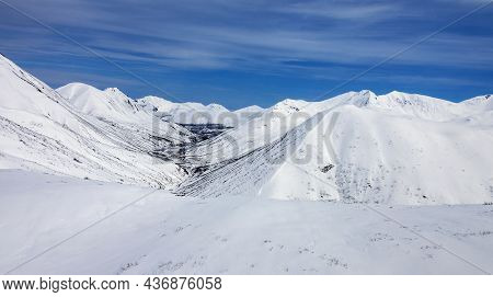 View Of The Mountain Landscape Under The Blue Sky After Spring Snowfall. Snow-covered Mountain Terra