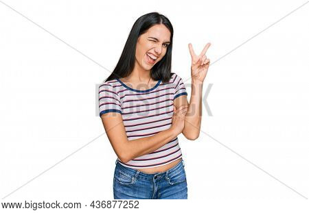 Young hispanic girl wearing casual striped t shirt smiling with happy face winking at the camera doing victory sign. number two.