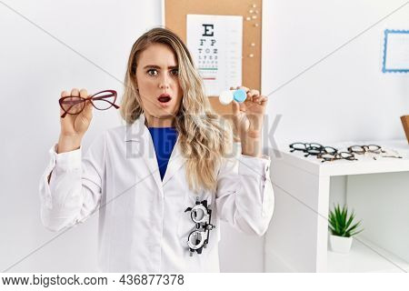Young beautiful optician woman holding glasses and contact lenses in shock face, looking skeptical and sarcastic, surprised with open mouth