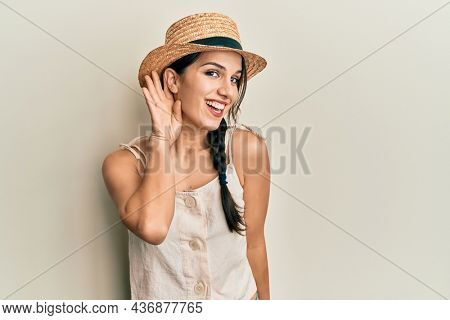 Young hispanic woman wearing summer hat smiling with hand over ear listening and hearing to rumor or gossip. deafness concept.