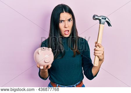 Young brunette woman holding piggy bank and hammer in shock face, looking skeptical and sarcastic, surprised with open mouth